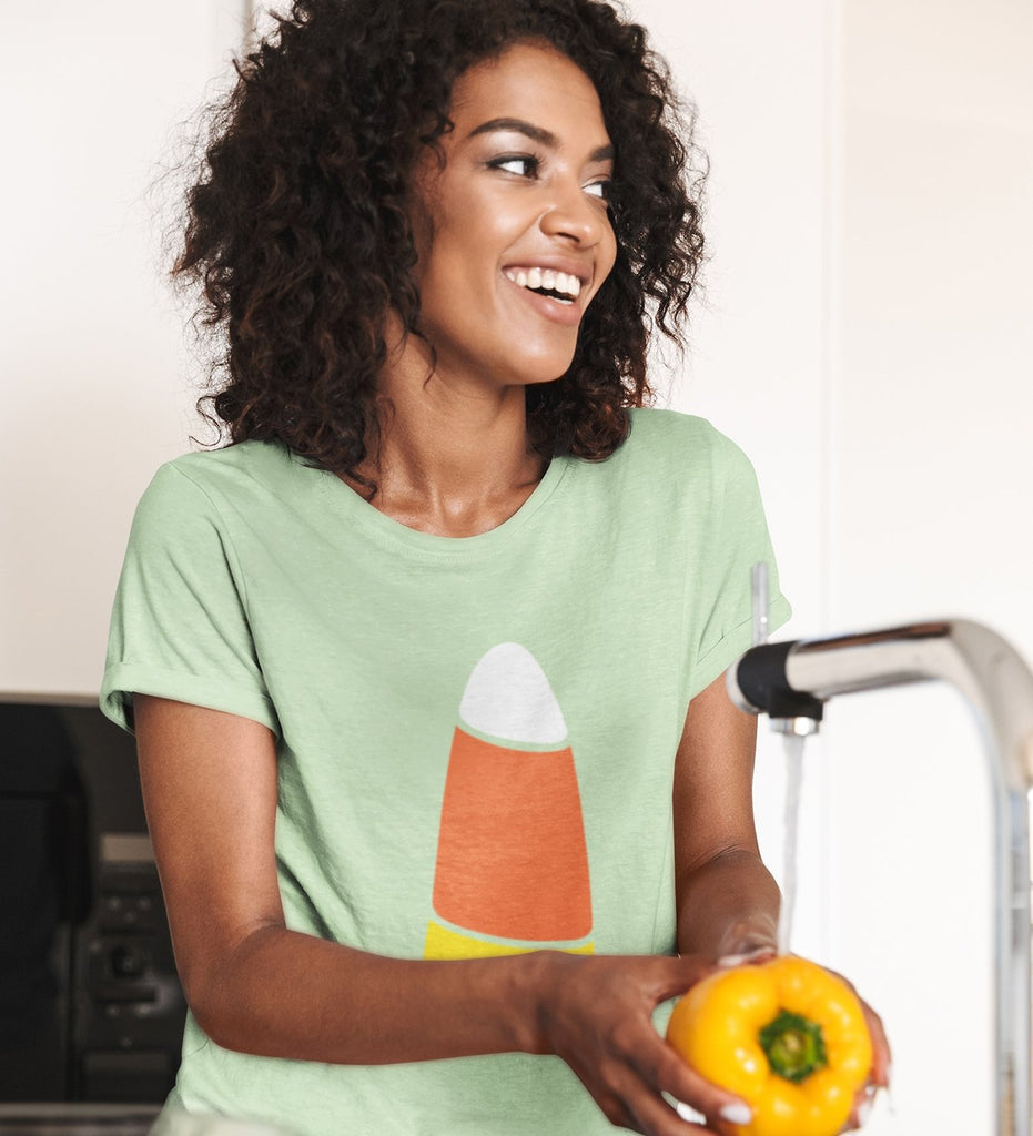 Woman wearing candy corn t-shirt washing veges in kitchen.
