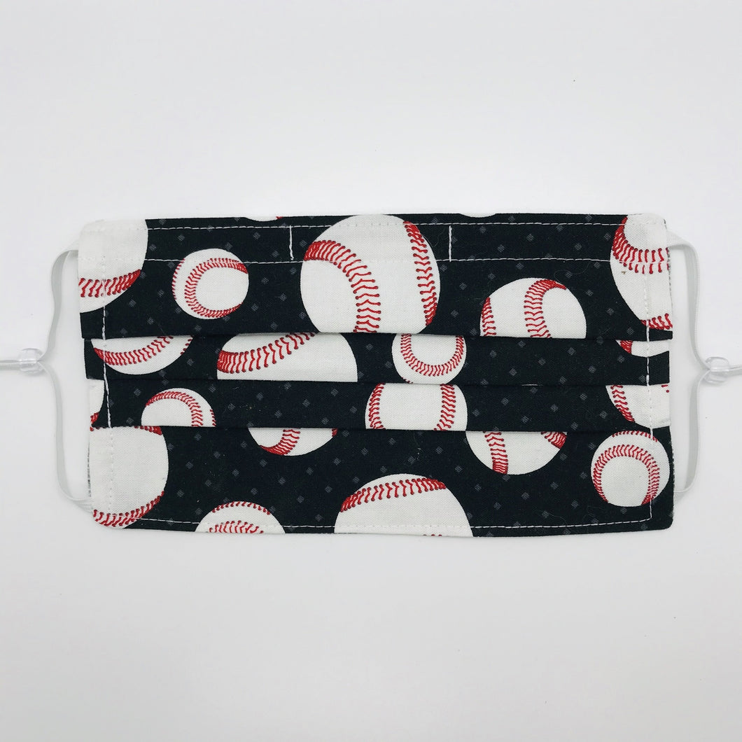 "Made with three layers of baseballs on black print 100% quilting cotton, this mask includes a filter pocket located in the pleats in the back of the mask for a filter of your choice, adjustable elastic ear loops and a bendable aluminum nose. Machine wash and dry after each use. 7"" H x 7.5"" W"