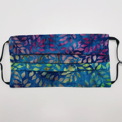 "Masks have three layers of 100% cotton with blue, green and purple leaves batik and include a filter pocket located in the pleats in the back of the mask for a filter of your choice. Masks have adjustable elastic ear loops and an aluminum nose piece. Machine wash and dry after each use. 7"" H x 7.5"" W"