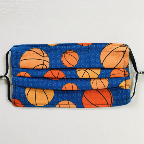 "100% quilting-weight sports themed print cotton fabric face mask with adjustable elastic ear loops and bendable nose piece. Washable, reusable fabric face mask. Wash in washing machine and dry in dryer after each use. 7"" H x 7.5"" W  These tossed basketballs on blue are from the fabric Collection: Sports Life by Robert Kaufman Fabrics"