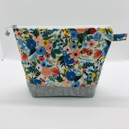 "The pouch is made from 100% quilting cotton by Rifle Paper Co and features a multicolored woodland floral print, Kaufman Essex cotton/linen for the base, and a layer of fleece. The cute metal tassel gives an added touch. 7.5 W x 6""H x 2.5""D. Machine washable and dryer safe, or air dry."