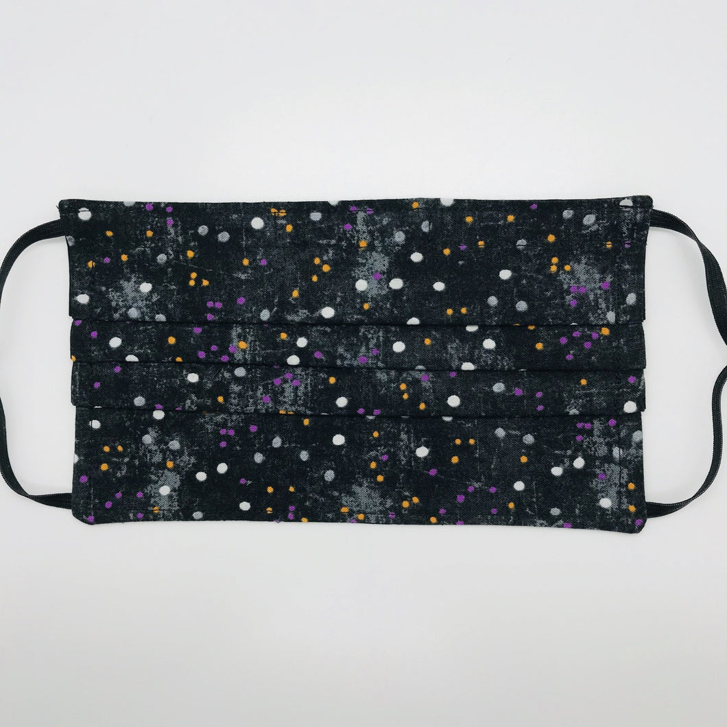 "Made with three layers of small white, gold and purple dots on black print 100% quilting cotton, this mask includes a filter pocket located in the pleats in the back of the mask for a filter of your choice, adjustable elastic ear loops and a bendable aluminum nose. Machine wash and dry after each use. 7"" H x 7.5"" W"