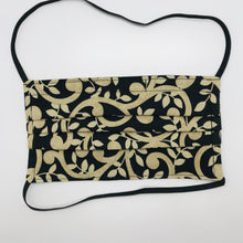 "Load image into Gallery viewer, Masks are made of 2 layers 100% quilting cotton featuring a gold swirls on black print, over the head elastic loops and a bendable aluminum nose. Wash in washing machine and dry in dryer after each use. 7"" H x 7.5"" W."
