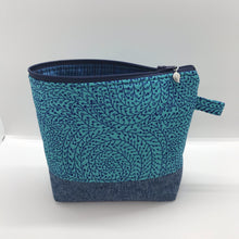 "Load image into Gallery viewer, The pouch is made from 100% quilting cotton with a blue/teal vine maze print, Kaufman Essex cotton/linen for the base, and a layer of fleece. The cute metal tassel gives an added touch. 7.5 W x 6""H x 2.5""D. Machine washable and dryer safe, or air dry."