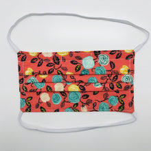 "Load image into Gallery viewer, Masks are made of 2 layers of flowers on orange print 100% quilting cotton and have behind the head elastic bands. The masks also have a bendable aluminum nose. Wash in washing machine and dry in dryer after each use. 7"" H x 7.5"" W"