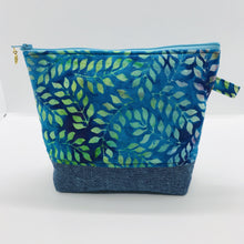 "Load image into Gallery viewer, The pouch is made from 100% batik quilting cotton with a blue, purple and green leaves print, Kaufman Essex cotton/linen for the base, and a layer of fleece. The cute metal tassel gives an added touch. 7.5 W x 6""H x 2.5""D. Machine washable and dryer safe, or air dry."