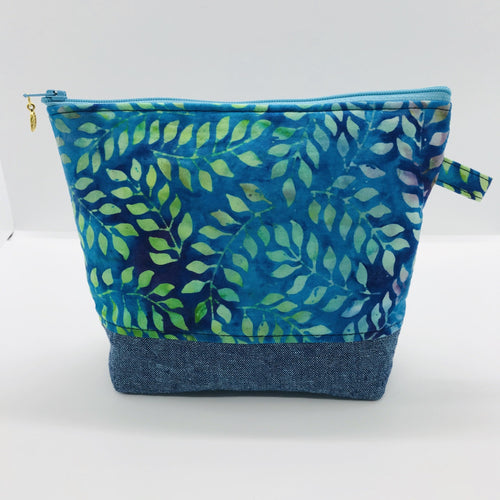 "The pouch is made from 100% batik quilting cotton with a blue, purple and green leaves print, Kaufman Essex cotton/linen for the base, and a layer of fleece. The cute metal tassel gives an added touch. 7.5 W x 6""H x 2.5""D. Machine washable and dryer safe, or air dry."
