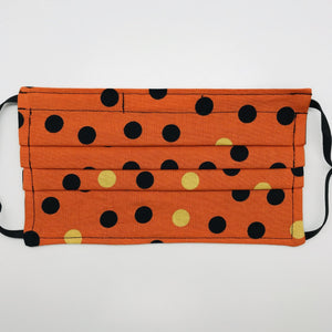 "Masks are made of 2 layers 100% quilting cotton featuring a print of black and gold dots on orange, adjustable elastic ear loops and a bendable aluminum nose. Wash in washing machine and dry in dryer after each use. 7"" H x 7.5"" W"