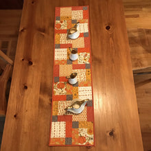 "Load image into Gallery viewer, Beautiful fall colors table runner. 100% cotton, disappearing nine patch design. free-motion quilted in circular design. machine wash cold, line dry. 44"" L x 11.5"" W"