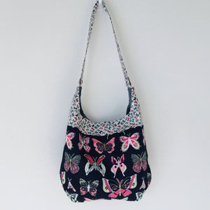 "Light weight and roomy this tote is made of soft and smooth Art Gallery butterfly print cotton, and lined with Essex cotton/linen from Robert Kaufman. The inner compartment has a magnetic snap and inner pocket. 15.5"" W & 14""H Total length with strap 33"""