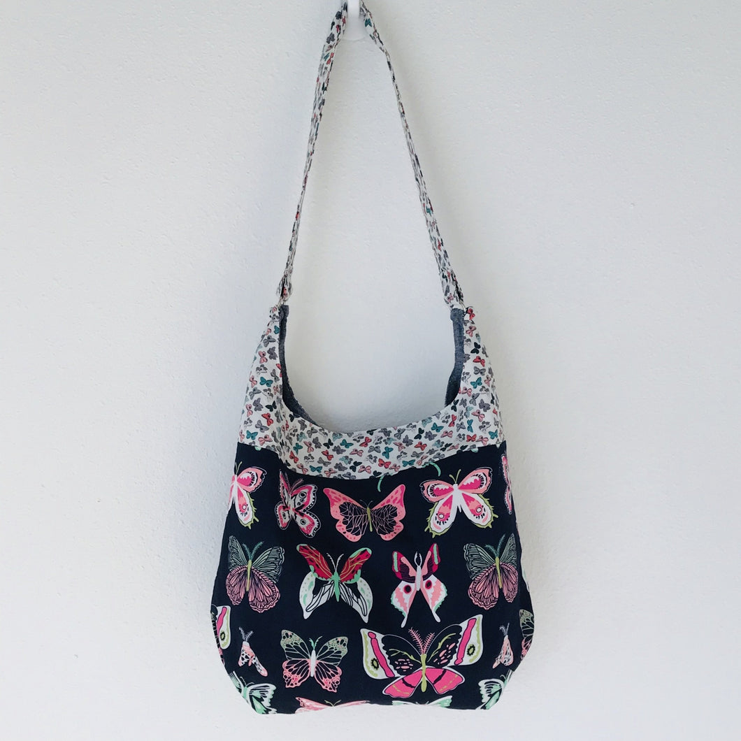 "Light weight and roomy this tote is made of soft and smooth Art Gallery butterfly print cotton, and lined with Essex cotton/linen from Robert Kaufman. The inner compartment has a magnetic snap and inner pocket. 15.5"" W & 14""H Total length with strap 33"