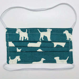 "Made with three layers of white dogs on green print 100% quilting cotton, this mask includes a filter pocket located in the pleats in the back of the mask for a filter of your choice, elastic head bands and a bendable aluminum nose. Machine wash and dry after each use. 7"" H x 7.5"" W"
