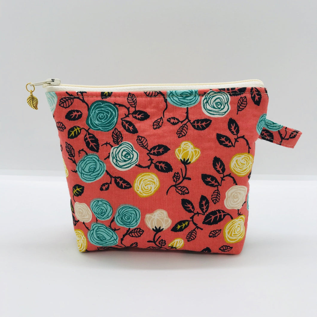 "The pouch is made from 100% cotton flowers on orange print and has a layer of fleece for structure and a cute metal tassel. The pouch design is from the Becca Bags pattern from Lazy Girl Design.  6""W x 4.5"" H x 1""D. Machine washable and dryer safe or air dry."