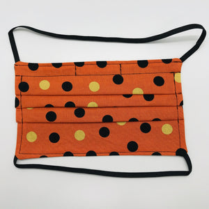 "Made with three layers of orange and gold dots on black print 100% quilting cotton, this mask includes a filter pocket located in the pleats in the back of the mask for a filter of your choice, over the head elastic loops and a bendable aluminum nose. Machine wash and dry after each use. 7"" H x 7.5"" W"