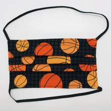 "Load image into Gallery viewer, Made with three layers of basketballs on black print 100% quilting cotton, this mask includes a filter pocket located in the pleats in the back of the mask for a filter of your choice, elastic head bands and a bendable aluminum nose. Machine wash and dry after each use. 7"" H x 7.5"" W"