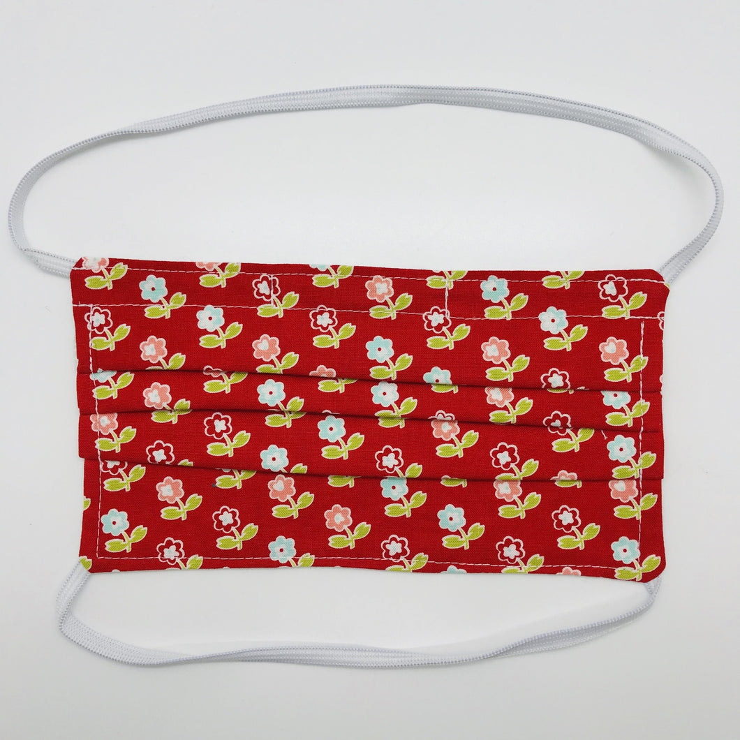 "Masks are made of 2 layers of 100% quilting-weight cotton with a vintage picnic flowers on red print  and have behind the head elastic bands. The masks also have a bendable aluminum nose piece which helps to make a better seal over the wearers face. Wash in washing machine and dry in dryer after each use. 7"" H x 7.5"" W"
