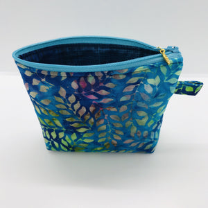 "The pouch is made of 100% batik quilting cotton of blue, purple and green leaves and a layer of fleece for stability. The cute metal tassel gives an added touch. 6""W x 4.5"" H x 1""D. Machine washable and dryer safe, or air dry."