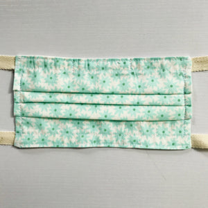 "100% quilting-weight aqua green cotton face mask with twill tape straps and bendable nose piece. Washable, reusable fabric face mask. Wash in washing machine and dry in dryer after each use.  Fabric from the Pond collection by Elizabeth Hartman  7"" H x 7.5"" W"