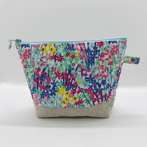 "The pouch is made from 100% quilting cotton with a spring flower print, Kaufman Essex cotton/linen for the base, and a layer of fleece. The cute metal tassel gives an added touch.  7.5 W x 6""H x 2.5""D. Machine washable and dryer safe, or air dry."