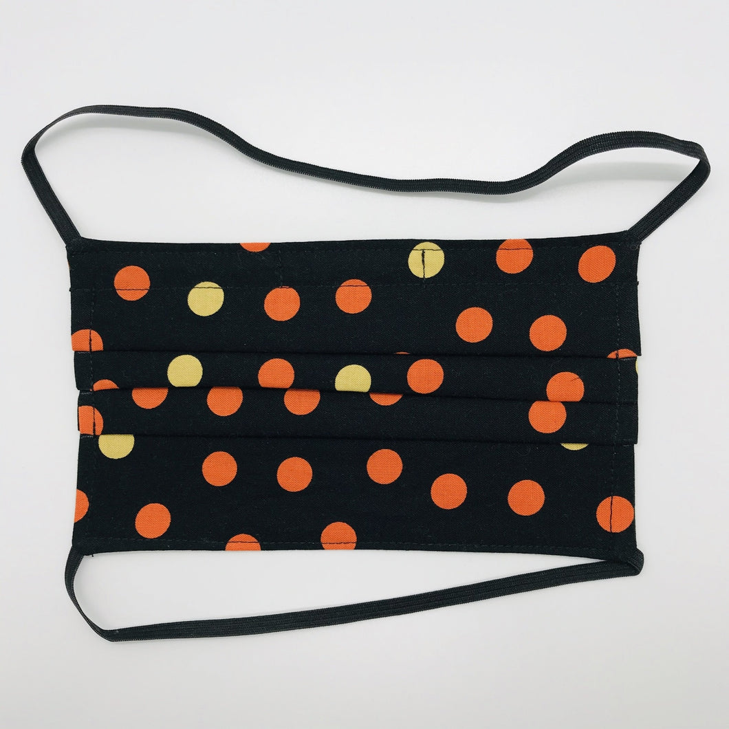 "Masks are made of 2 layers 100% quilting cotton featuring a print of orange and gold dots on black, over the head elastic loops and a bendable aluminum nose. Wash in washing machine and dry in dryer after each use. 7"" H x 7.5"" W"