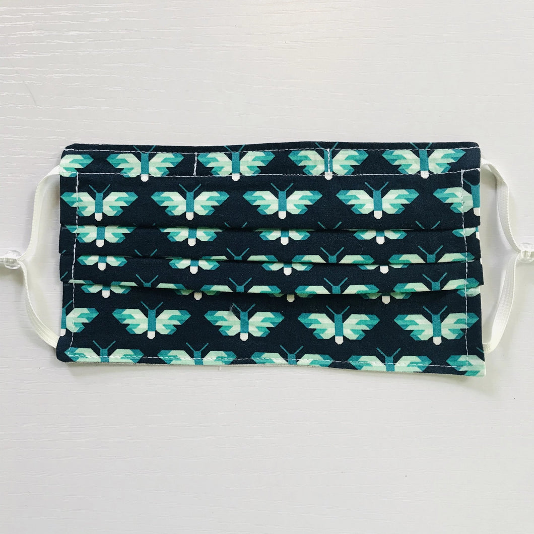 "100% quilting-weight blue and green animal themed cotton face mask with adjustable elastic ear loops and bendable nose piece. Washable, reusable fabric face mask. Wash in washing machine and dry in dryer after each use. 7"" H x 7.5"" W  Butterflies in Ultra Marine - Pacific Collection - Elizabeth Hartman (designer)-Robert Kaufman Fabrics"