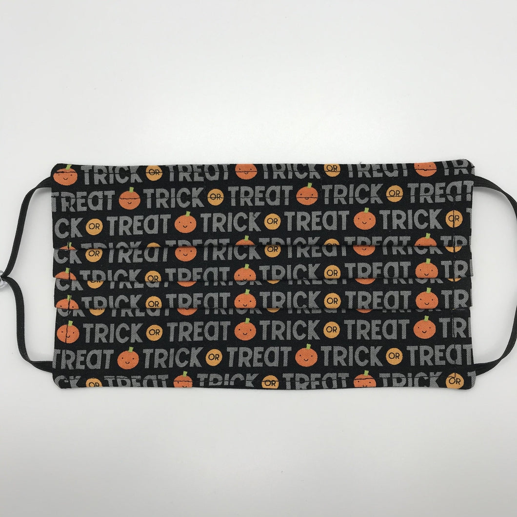 "Made with three layers of trick or treat words on orange pumpkins on black print 100% quilting cotton, this mask includes a filter pocket located in the pleats in the back of the mask for a filter of your choice, adjustable elastic ear loops and a bendable aluminum nose. Machine wash and dry after each use. 7"" H x 7.5"" W"