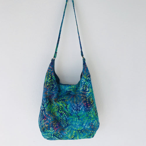 "This beautiful 100% green, blue and purple leaves cotton batik makes a great slouch bag that is light and durable. The lining is beautiful Essex cotton\linen from Robert Kaufman and has a magnetic snap and inner pocket. 15.5"" W & 14""H. Total length with strap 33"""