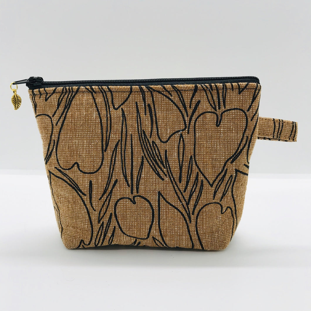 "The pouch is made from Roasted Pecan Essex linen/cotton from the Driftless collection by Anna Graham for Robert Kaufman Fabrics and a layer of fleece. The cute metal tassel gives an added touch. 6""W x 4.5"" H x 1""D. Machine washable and dryer safe, or air dry."