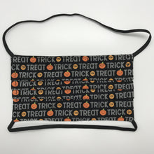 "Load image into Gallery viewer, Masks are made of 2 layers 100% quilting cotton featuring a print of trick or treat words on black, over the head elastic loops and a bendable aluminum nose. Wash in washing machine and dry in dryer after each use. 7"" H x 7.5"" W"
