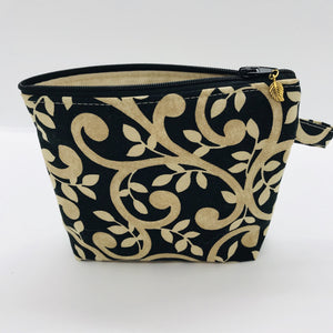 "The small pouch is made from 100% gold swirls on black print and has a layer of fleece for structure and a cute metal tassel. The pouch design is from the Becca Bags pattern from Lazy Girl Design. 6""W x 4.5"" H x 1""D. Machine washable and dryer safe or air dry."