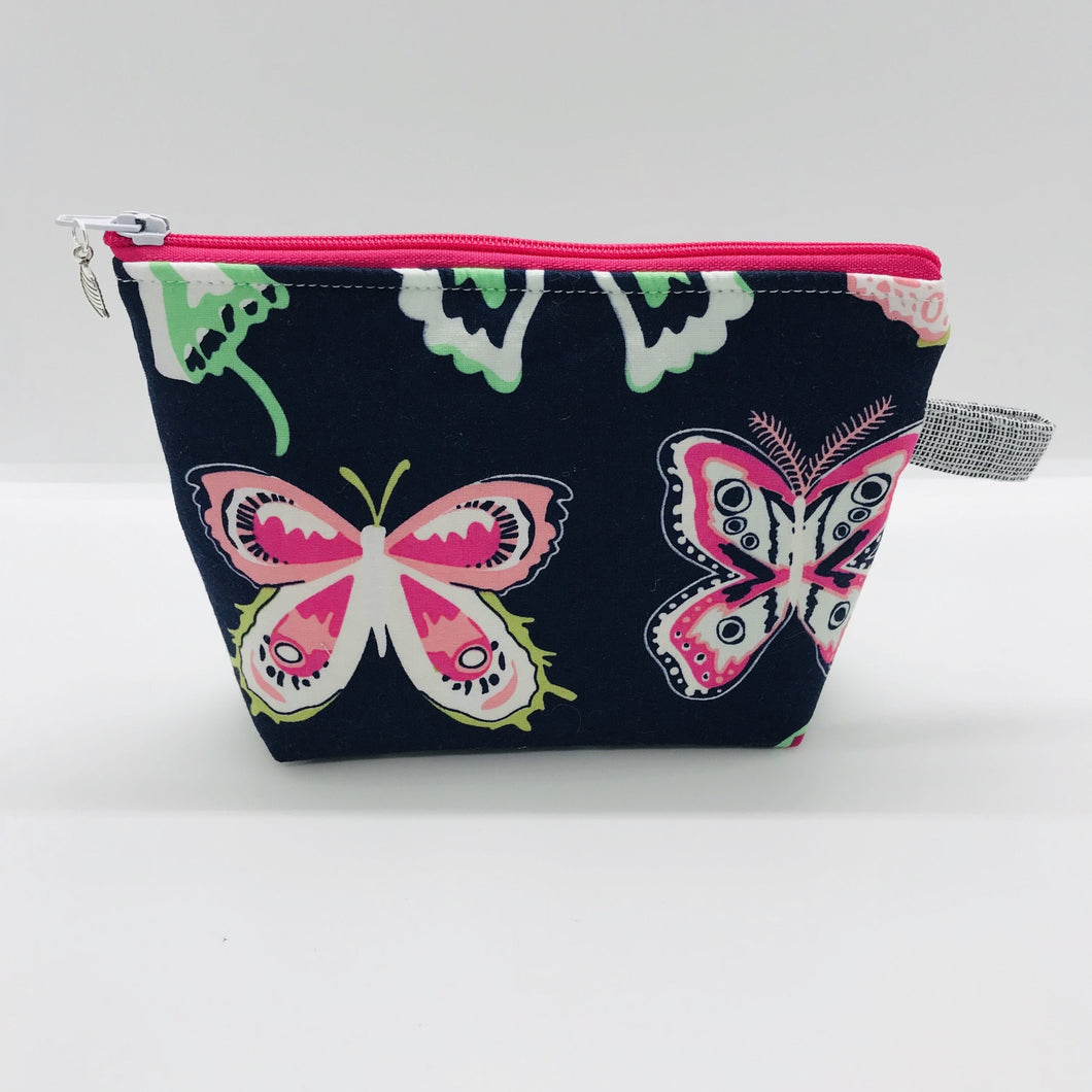 "The pouch is made of 100% quilting cotton from Art Gallery features a large pink and white butterflies on navy print and a layer of fleece for stability. The cute metal tassel gives an added touch. 6""W x 4.5"" H x 1""D. Machine washable and dryer safe, or air dry."