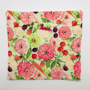 Image of a garden veggies and flower cotton print in green, oranges and pinks.
