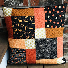 Load image into Gallery viewer, Scrappy Halloween pillow cover, 100% cotton in orange, black and gold prints. The pillow is quilted with a meandering design by machine with 40 wt Aurifil thread and has a hidden zipper in the back made of black Kona Cotton. The pillow cover only is offered and does not include the pillow form insert. The pillow insert needed is 18 x 18 inches. Machine wash with like colors in cold water with low suds soap such as Woolite, line dry.