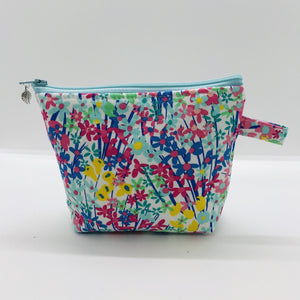 "The small pouch is made from 100% cotton spring flowers print and has a layer of fleece for structure and a cute metal tassel. The pouch design is from the Becca Bags pattern from Lazy Girl Design. 6""W x 4.5"" H x 1""D. Machine washable and dryer safe or air dry."