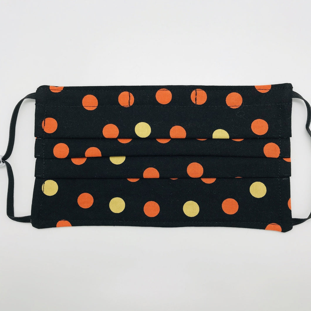 "Made with three layers of orange and gold dots on black print 100% quilting cotton, this mask includes a filter pocket located in the pleats in the back of the mask for a filter of your choice, adjustable elastic ear loops and a bendable aluminum nose. Machine wash and dry after each use. 7"" H x 7.5"" W"