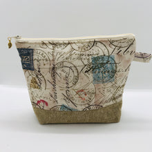 "Load image into Gallery viewer, The pouch is made from 100% quilting cotton with tan antique stamp print, Kaufman Essex cotton/linen for the base, and a layer of fleece. The cute metal tassel gives an added touch. 7.5 W x 6""H x 2.5""D. Machine washable and dryer safe, or air dry."