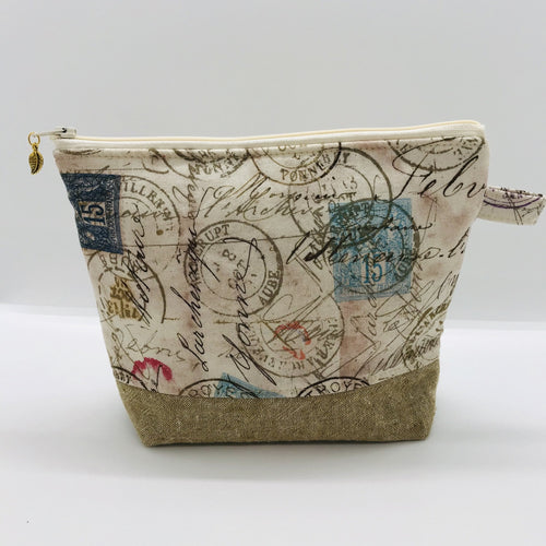 "The pouch is made from 100% quilting cotton with tan antique stamp print, Kaufman Essex cotton/linen for the base, and a layer of fleece. The cute metal tassel gives an added touch. 7.5 W x 6""H x 2.5""D. Machine washable and dryer safe, or air dry."