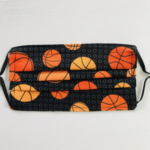 "100% quilting-weight sports themed print cotton face mask with adjustable elastic ear loops and bendable nose piece. Washable, reusable fabric face mask. Wash in washing machine and dry in dryer after each use. 7"" H x 7.5"" W  These tossed basketballs on black are from the fabric collection: Sports Life by Robert Kaufman Fabrics"