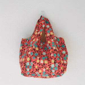 "The tote is made of 100% quilting cotton featuring  a green, yellow and white flowers on orange print and is fully lined. Machine washable and dryable or hang dry.  Size: 17"" x 21""."