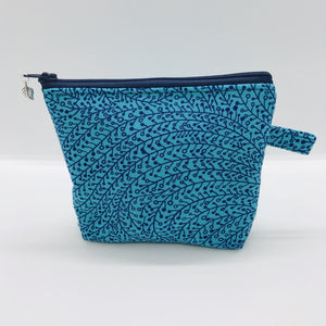 "The small pouch is made from 100% blue/teal vine maze print and has a layer of fleece for structure and a cute metal tassel. The pouch design is from the Becca Bags pattern from Lazy Girl Design. 6""W x 4.5"" H x 1""D. Machine washable and dryer safe or air dry."