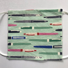 "Load image into Gallery viewer, 100% quilting-weight aqua green novelty print cotton face mask with adjustable elastic ear loops and bendable nose piece. Washable, reusable fabric face mask. Wash in washing machine and dry in dryer after each use. 7"" H x 7.5"" W  Fabric Collection - Cotton + Steel - Trinket Pens Aqua"
