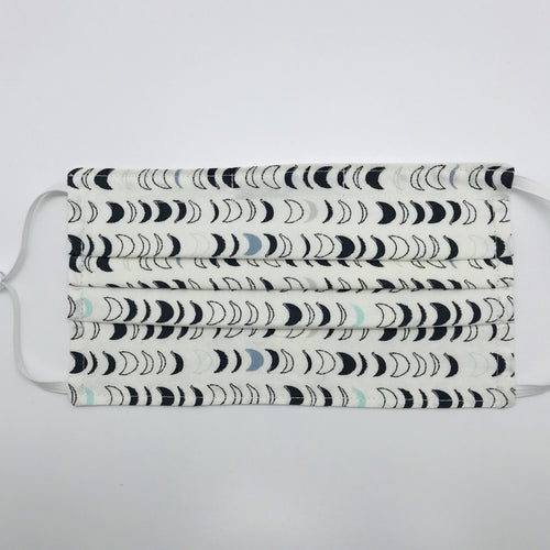 "Masks are made of 2 layers 100% quilting cotton featuring blue, white and black half moons in rows on white print, adjustable elastic ear loops and a bendable aluminum nose. Wash in washing machine and dry in dryer after each use. 7"" H x 7.5"" W"