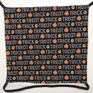 Image of Trick or Treat works and pumpkins on black fabric print.