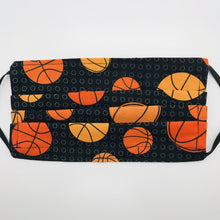 "Load image into Gallery viewer, Made with three layers of basketballs on black print 100% quilting cotton, this mask includes a filter pocket located in the pleats in the back of the mask for a filter of your choice, adjustable elastic ear loops and a bendable aluminum nose. Machine wash and dry after each use. 7"" H x 7.5"" W"