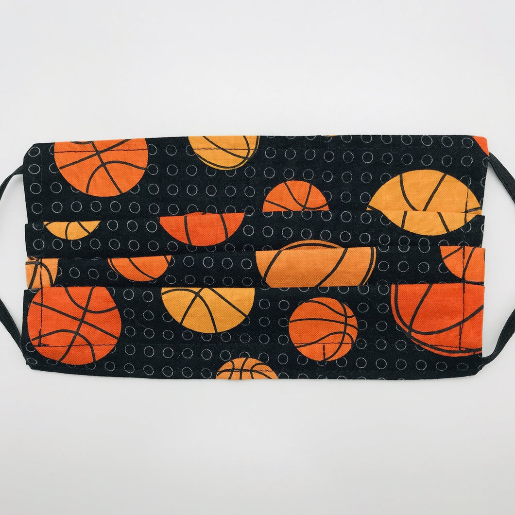 "Made with three layers of basketballs on black print 100% quilting cotton, this mask includes a filter pocket located in the pleats in the back of the mask for a filter of your choice, adjustable elastic ear loops and a bendable aluminum nose. Machine wash and dry after each use. 7"" H x 7.5"" W"