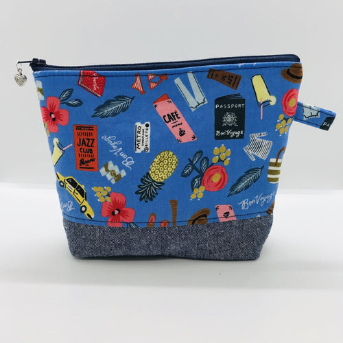 "The pouch is made from 100% quilting cotton with a blue travel themed print, Kaufman Essex cotton/linen for the base, and a layer of fleece. The cute metal tassel gives an added touch. 7.5 W x 6""H x 2.5""D. Machine washable and dryer safe, or air dry."