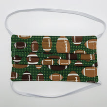 "Load image into Gallery viewer, Made with three layers footballs on green print 100% quilting cotton, this mask includes a filter pocket located in the pleats in the back of the mask for a filter of your choice, elastic head bands and a bendable aluminum nose. Machine wash and dry after each use. 7"" H x 7.5"" W"