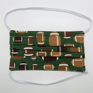 "Made with three layers footballs on green print 100% quilting cotton, this mask includes a filter pocket located in the pleats in the back of the mask for a filter of your choice, elastic head bands and a bendable aluminum nose. Machine wash and dry after each use. 7"" H x 7.5"" W"