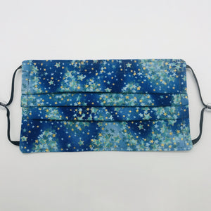 "The masks are made of 100% quilting-weight cotton featuring a blue and green with gold stars print. The masks have adjustable elastic ear loops and a bendable nose piece. Machine wash and dry after each use. 7"" H x 7.5"" W"