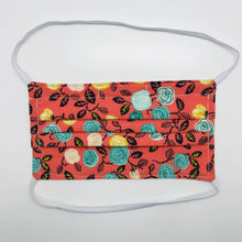"Load image into Gallery viewer, Made with three layers of flowers on orange print 100% quilting cotton, this mask includes a filter pocket located in the pleats in the back of the mask for a filter of your choice, elastic head bands and a bendable aluminum nose. Machine wash and dry after each use. 7"" H x 7.5"" W"